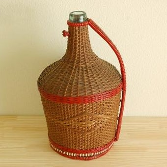 スウェーデンで見つけた籐とビニールストロー素材を編んだカバー付きのガラス瓶(大きなピッチャー)の商品写真