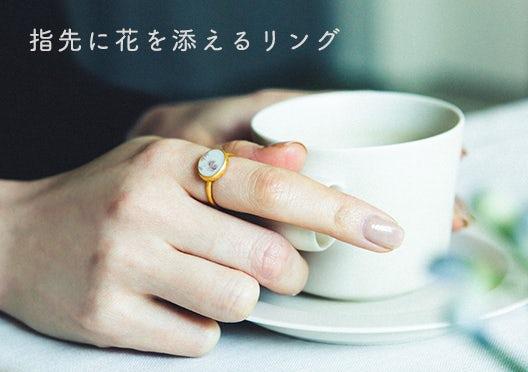 指先に花を添えるリングの画像